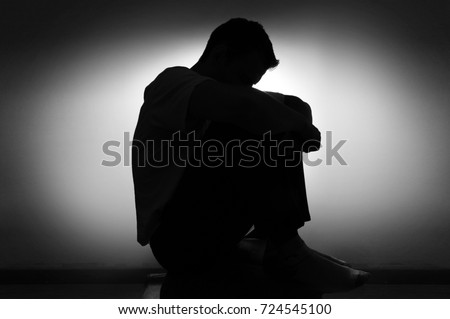 sad silhouette of a man in depression sitting on a chair with his head down