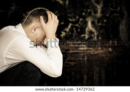 sad sitting young businessman with grunge wall background, copy space for the text