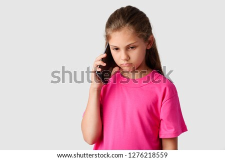 Sad small girl talking on modern mobile phone in a studio. Unhappy little schoolgirl heard bad news from her relatives by smartphone. Gloomy girl looking down uses mobile phone to communicate