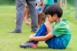 Sad soccer kid sitting on field side substitution bench doesn't get to play in a competition match