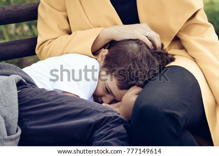 Sad son comforting in mother's lap. Shy little boy hiding in mother's embrace.