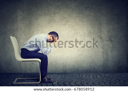 Sad stressed businessman sitting in an empty office