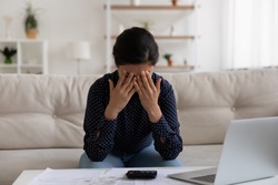 Sad stressed young indian female deal with bankruptcy of her small business having huge loan mortgage debt. Upset depressed mixed race woman crying at home office after losing money in fraudulent deal