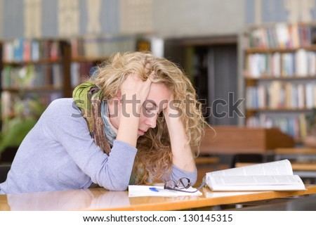 sad student  working in library
