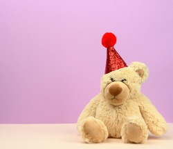 sad teddy beige bear in a red cap sits on a purple background, a place for an inscription