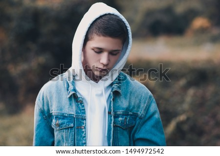 Sad teen boy 14-16 year old wearing white hoodie and denim jacket in dark outdoors. Depressed mood. Loneliness.