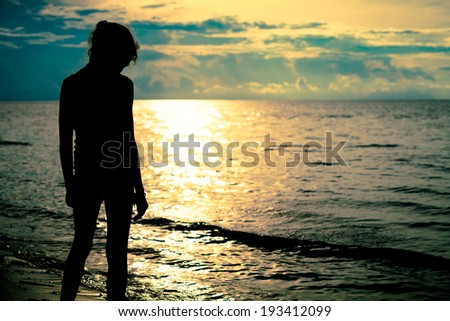 sad teen girl standing on the beach at the dawn time