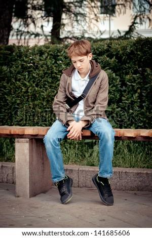 Sad teen sitting on bench in park