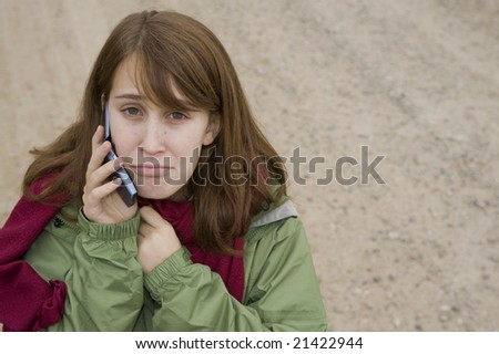 Sad teenage girl on a gravel  road, talking on her cell phone