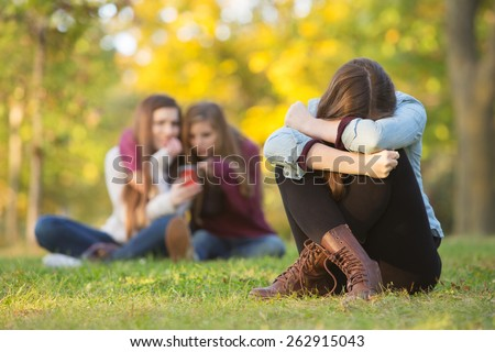 Sad teenage woman sitting with head down near laughing group