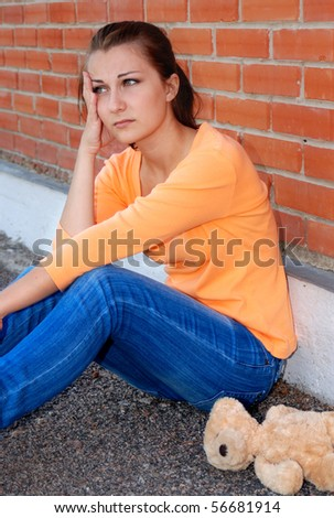 Sad teenager girl with teddy bear sitting near brick wall - stock photo