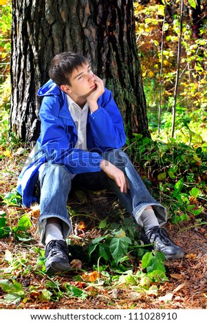 sad teenager is thinking in the autumn forest