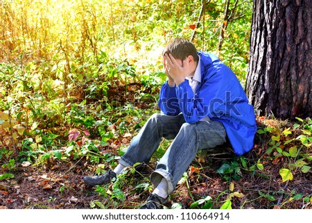 sad teenager sitting in the autumn forest alone #110664914