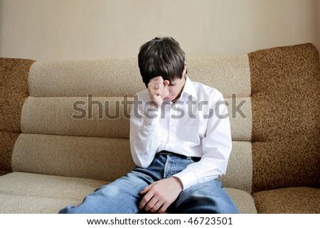 sad teenager sitting on the sofa