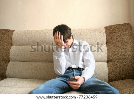 sad teenager sitting on the sofa with mobile phone