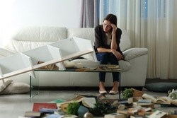 Sad tenant complaining after home robbery sitting on a couch in the night with messy living room