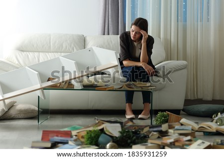 Sad tenant complaining after home robbery sitting on a couch in the night with messy living room ストックフォト ©