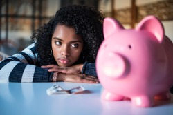 Sad thoughtful frustrated black woman with piggy bank