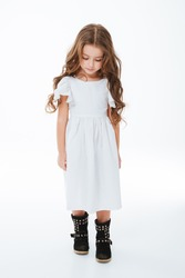 Sad tired little girl with curly long hair walking and looking down over white background