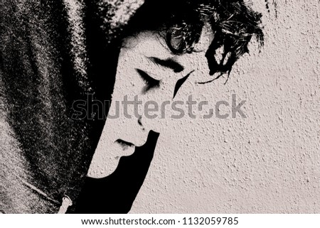 Sad troubled teenager school boy with hood on posing outdoor sitting alone on the street - stock photo made like graffiti stencil painting on white concrete wall stock photo