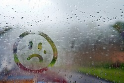 Sad unhappy face drawn on fogged glass on a wet rainy grey window soft light grey skies