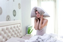 Sad unhappy woman suffering and disturbed from noisy neighbors and covering her ears with pillow while trying to falling sleep in bed at home in early morning.