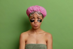 Sad unhappy young Afro American woman has sulking face expression applies beauty patches under eyes to reduce puffiness wrapped in bath towel isolated over green background. Hygiene concept.