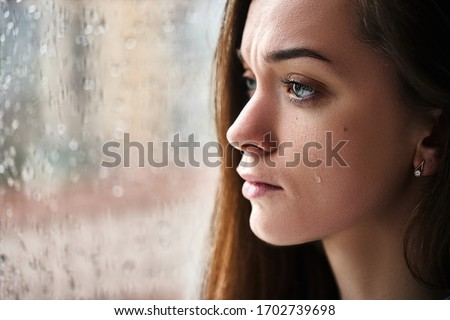 Sad upset crying woman with tears eyes suffering from emotional shock, loss, grief, life problems and break up relationship near window with raindrops. Female received bad news