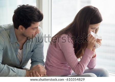 Sad upset girl crying, wiping tears with handkerchief, friend or boyfriend trying to comfort her at home, husband consoling depressed wife, support in difficult situation, compassion or apologize