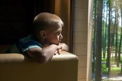 Sad upset waiting boring depressed child (boy) near a window