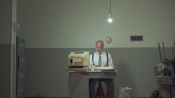Sad vintage style businessman working in a small rundown office with an outdated computer, he feels frustrated and disappointed