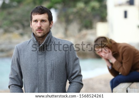 Sad wife complaining after break up sitting on the beach and angry husband leaving her in winter Foto d'archivio ©