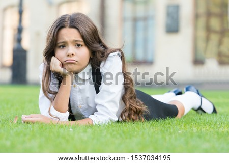 Sad without a smile. Sad schoolgirl relax on green grass. Adorable little child with sad emotion on face. Feeling sad and unhappy. Sadness and depression. School problems.