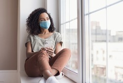 Sad woman alone during coronavirus pandemic wearing face mask indoors at home for social distancing. Mixed race girl looking at window. Anxiety, stress, lockdown, mental health crisis concept