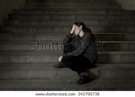 sad woman alone on street subway staircase suffering depression looking looking sick and helpless sitting lonely as female victim of abuse concept  in  dark urban night grunge background  #343700738