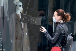 Sad woman at the entrance to a closed clothing store in a shopping center in a mask on her face. Closed store, shop because of Quarantine, coronavirus, covid-19. Sign Closed on the door