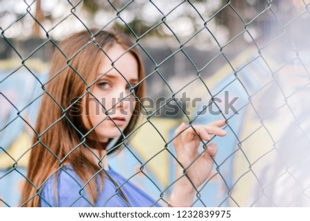 Sad woman behind the fence #1232839975