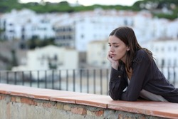 Sad woman complaining alone looking down in a balcony in a town on the beach