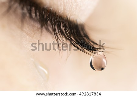 Sad woman concept - closed eyelid closeup with a teardrop on eyelashes.  A tear on eyes macro close-up. A tear runs down his cheek. Tinted beige.