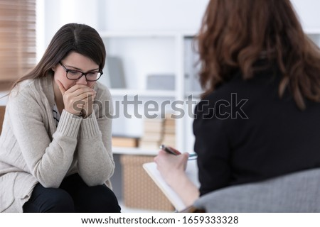 Sad woman crying during psychotherapy at professional clinic Foto stock ©