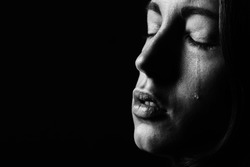 sad woman crying on black background, closeup portrait, monochrome