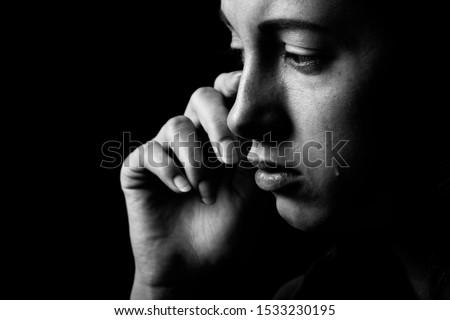 sad woman crying on black background, looking down, closeup portrait, monochrome Foto stock ©