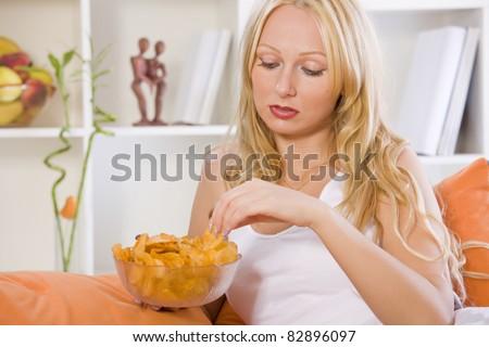 sad woman eating snacks at home while sitting on sofa