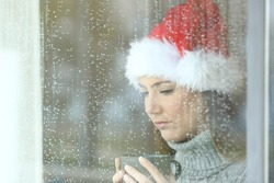 Sad woman in christmas looking down through a windos in a rainy day