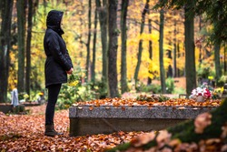 Sad woman is mourning for dead person at grave in cemetery. Lonely mourner in autumn graveyard.  Grief and cry for dead people