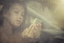 Sad woman looking in the mobile phone and reading massega in the window with rain drop in the car. Face of young female behind rain car window. Loneliness and depression concept. Psychology