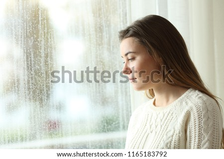 Sad woman looking outdoors through a window in a rainy day at home