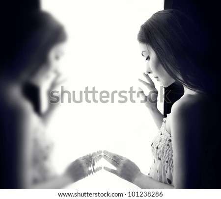 sad woman looking through the window. - stock photo