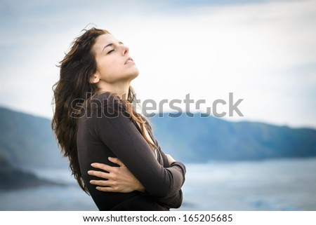 Sad woman shivering and feeling the sea breeze. Nostalgic and emotional female hugging herself and feeling low on cold late summer or autumn day. Beautiful curly hair caucasian model.