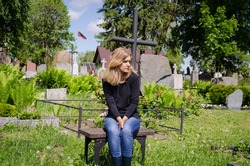 Sad woman sit near lover grave in cemetery. Patriot soldier died. National Lithuania flag.